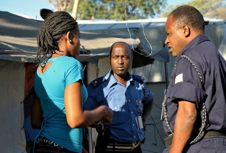 A woman in the Petionville Camp at the edge of Port au Prince, Haiti, is interviewed by police officials after lodging a domestic violence complaint against her husband. Copyright: Paul Jeffrey
